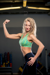 portrait of an athlete blonde in a gym showing biceps