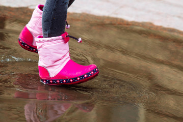 little girl in pink rubber boots in puddle.
