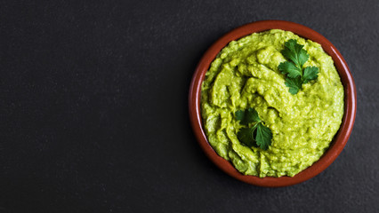 Guacamole spread  in clay bowl on a black background. Avocado sauce. Top view with copy space.