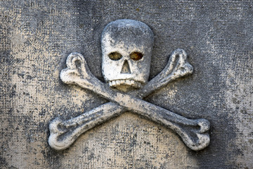 Figure of skull and crossbones on tombstone in little graveyard on island Brac in Croatia