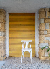 Traditional Egyptian white wooden chair over background of bricks stone wall and yellow roll-up door