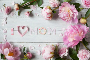 Background to Mother's Day with congratulations and pink peonies and roses