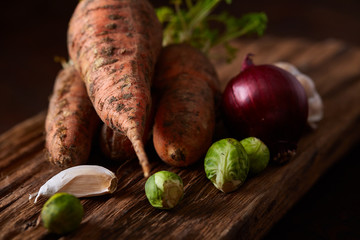 Organic farm vegetables with fresh carrots on flat piece of wood over rustic background, top view, selective focus