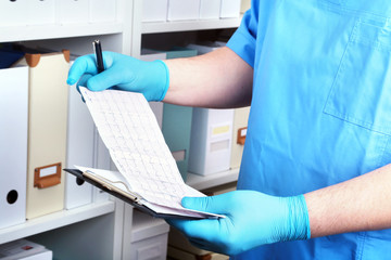 Doctor in a white coat write to the folder on a background of a shelf with folders