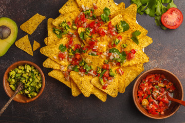 Mexican food concept. Nachos - yellow corn totopos chips with various sauces in wooden bowls: guacamole sauce and tomato sauce, top view