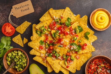 Mexican food concept. Nachos - yellow corn totopos chips with various sauces in wooden bowls: guacamole, cheese sauce, pico del gallo, top view