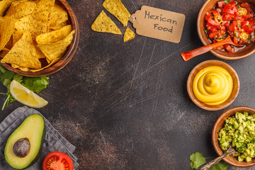 Mexican food concept. Nachos - yellow corn totopos chips with various sauces in wooden bowls: guacamole, cheese sauce, pico del gallo, frame of food, top view, copy space.