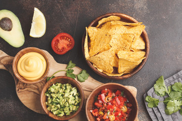 Mexican food concept. Nachos - yellow corn totopos chips with various sauces in wooden bowls: guacamole, cheese sauce, pico del gallo. Top view, food background