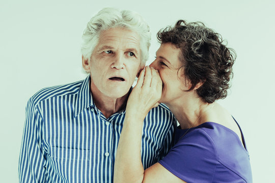 Mature woman telling secret to husband. She whispering in his ear. Surprised senior man attentively listening to wife. Studio shot. Relationship or gossip concept