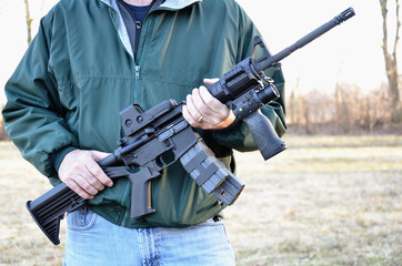 AR-15, M-4 style rifle being held.