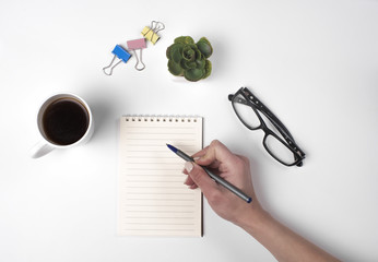 Young woman right hand writing on blank notebook on white table with coffee cup,  and glasses beside in morning time