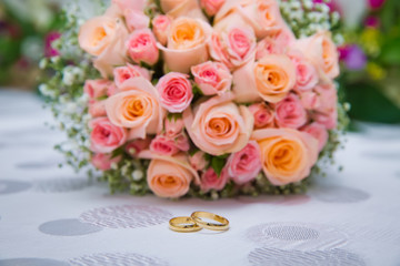Bridal bouquet with orange and pink roses of different size with handle on white background. Wedding bouquet with beautiful flowers. Two rings represent the meaning of feeling love. Selective focus