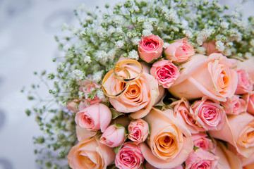 Bridal bouquet with orange and pink roses of different size with handle on white background. Romantic wedding bouquet with beautiful flowers. Two rings represent the meaning of feeling love