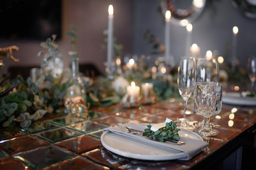 Mirror table served with plates, forks, spoons, glasses,  napkins in the restaurant. Beautiful festive table decorated with fresh flowers and candles