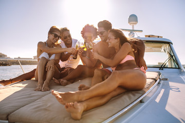 Young friends having drinks on the yacht deck Wall mural