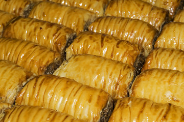 background - oriental sweets, baklava in the form of rolls lies in rows in a continuous layer
