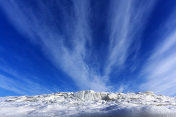 bright blue spring sky with cirrus clouds over melting ice and snow..