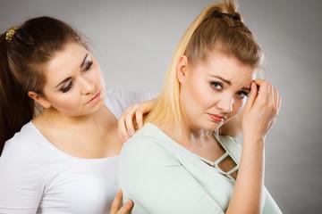Woman hugging her sad female friend