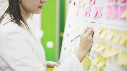 A doctor woman is writing down some information on the sticker in the laboratory. Yellow and pink stickers are on a board in front of a doctor woman, she is writing a data on the stickers