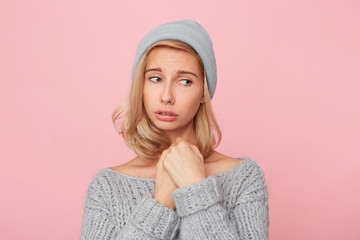 Close-up portrait of young blonde female, standing over pink background, keep her hands under chin and and miss her parents.