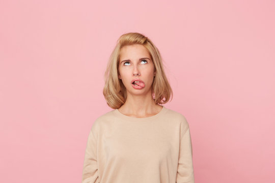 Bored to death! Young blonde female, feels drearily and looks above, shows her tongue with disgust. Isolated over pink background.