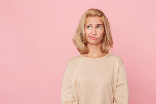 Indoor shot of doubtful pensive woman, looks aside, curves her lip, feels uncertain, try to make choice. Isolated, over pink background with copyspace