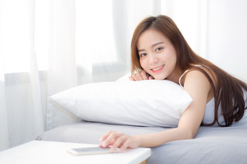 Beautiful young asian woman hand of turn off alarm on call mobile phone while wake up after sleep relax in good morning at bedroom.