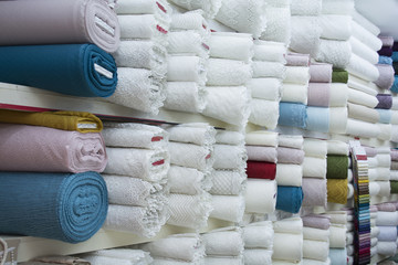 Rolls of white fabric and textiles in a factory shop. Multi different colors and patterns on the market