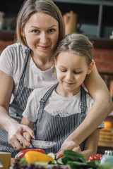 Adult woman looking at camera while helping to cook to young daughter.