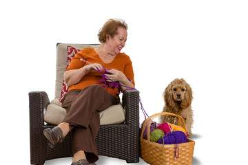 Happy smiling senior woman knitting with her dog