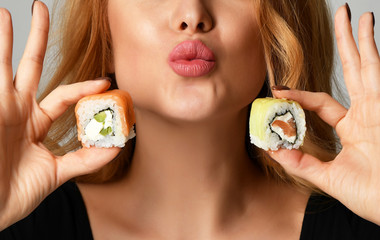 Closeup woman with sushi hold philadelphia rolls in hands show kissing sign on a light gray