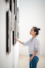 woman looking at the pictures on the wall