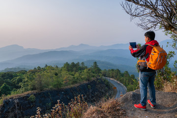 Thai Asian Man traveler looking to tablet and view mountain of doi inthanon national park