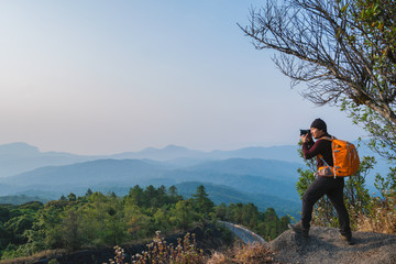 Thai Asian Man traveler take photo view mountain of doi inthanon national park with mirrorless camera