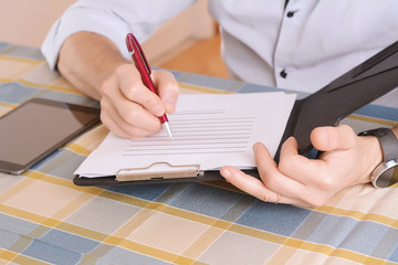 Close-up of businessman signing a document