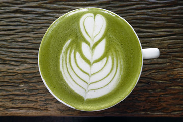 A cup of green tea matcha latte on wooden background