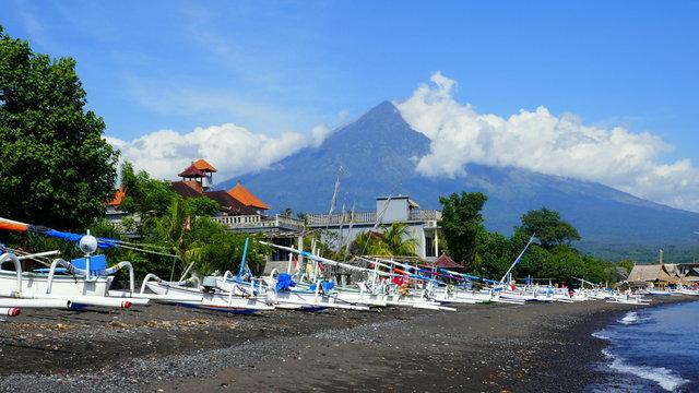Strand mit Fischerbooten in Amed (Bali) und Vulkan Agung im Hintergrund
