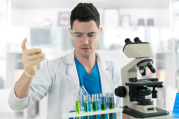 The scientist male working with a microscope and test tube
