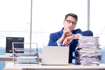 Businessman workaholic struggling with pile of paperwork