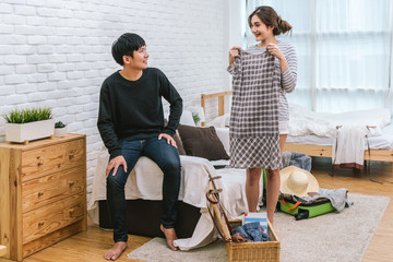 Happy Asian Couple choosing the clothes for preparing to travel in living room at the modern home, Couple, life style and traveler concept,