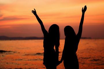Silhouette of two woman having fun on the sea beach