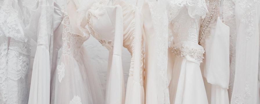 Banner White modern wedding dresses in dress store.