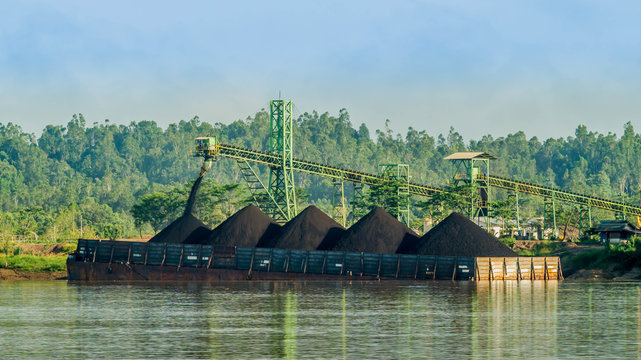 barge is loaded with coal using conveyor in the stockpile on the riverbank