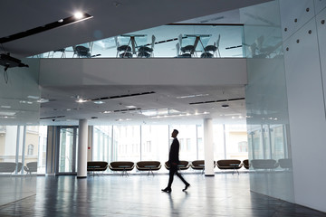 Profile view of confident businessman wearing suit walking along spacious office lobby with panoramic windows, motion shot