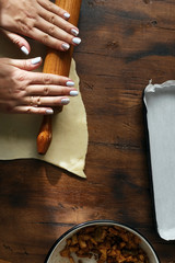 Fototapete - Female hands cooking apple strudel on dark rustic kitchen table, top view