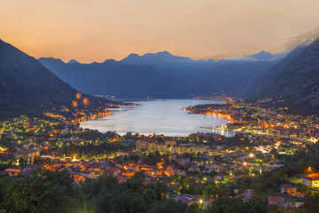 Sunset Bay of Kotor (Boka Kotorska) at Adriatic Sea, southwestern Montenegro. Night cities view with firework from Dinaric Alps