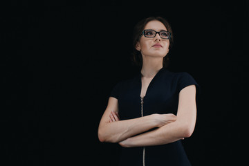 Portrait of attractive young caucasian business woman with crossed arms on black background