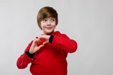 Cute confident excited little caucasian boy in red sweater showing love sign on grey background