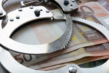 Financial crime in Europe Union. Euros and handcuffs.