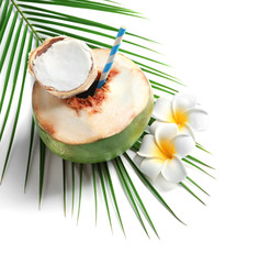 Fresh green coconut with drinking straw and flowers on white background